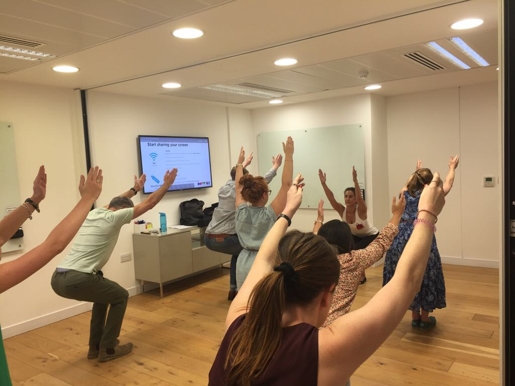 Standing yoga at Hotwire PR Moorgate Liverpool Street Utkatasana Chair Pose workplace yoga, office yoga, yoga everywhere, wellness week, desk yoga, chair yoga, corporate health and wellbeing champion, yoga London
