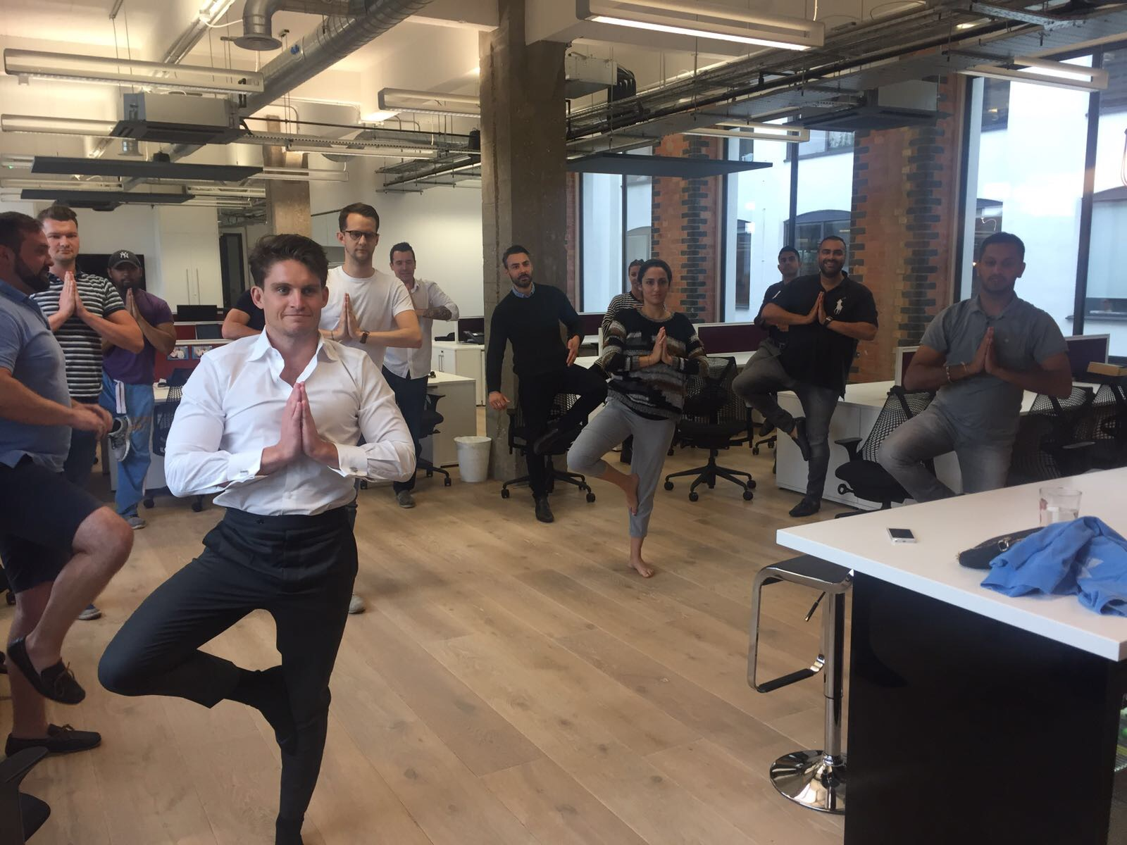 Standing yoga at Kau Media Group KMG Hammersmith Vrikshasana Vriksasana Tree Pose workplace yoga, office yoga, yoga everywhere, wellness week, desk yoga, chair yoga, corporate health and wellbeing champion, yoga London